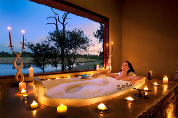 Indulgent candlelit bubble bath with scenic views.