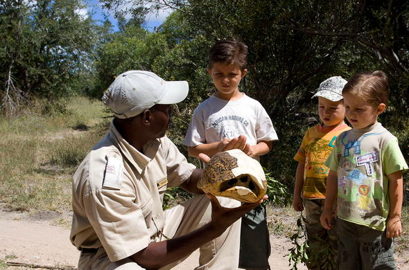 Guide teaching children on safari.