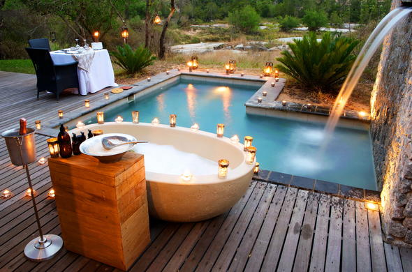 Private deck with romantic dinner and open air bath at Londolozi Granite Suites.